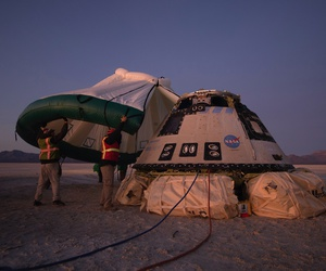 Boeing, NASA, and U.S. Army personnel work around the Boeing Starliner spacecraft shortly after it landed in White Sands, N.M., on Dec. 22, 2019.