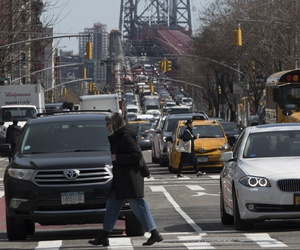 In this March 2019 photo, pedestrians cross Delancey Street as traffic is seen making its way into Manhattan from Brooklyn over the Williamsburg Bridge, in New York.