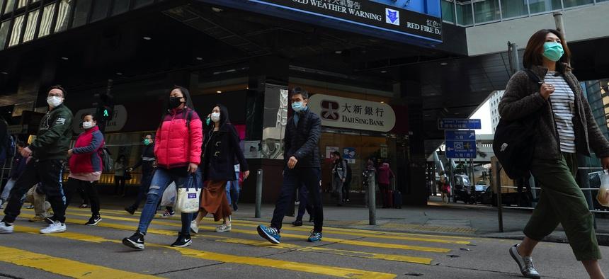 People wearing face masks walk at a downtown street in Hong Kong Monday, Feb. 17, 2020.