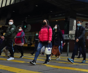 People wearing face masks walk at a downtown street in Hong Kong Monday, Feb. 17, 2020.