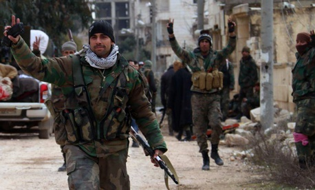 Syrian soldiers flash the victory sign in the Rashideen neighborhood, in Aleppo province, Syria, in this photo released Sunday, Feb. 16, 2020.
