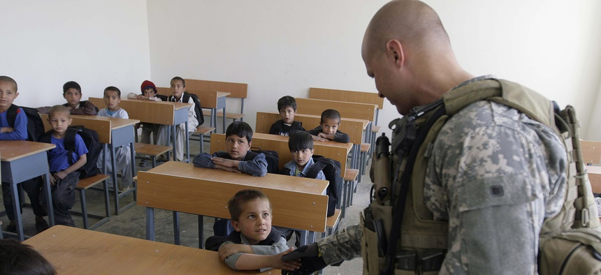 A US soldier of Combined Joint Special Operations Task Force Afghanistan shakes hand with an Afghan boy during the opening of a school in Bagram, north of Kabul, Afghanistan, Monday, March 24, 2008.