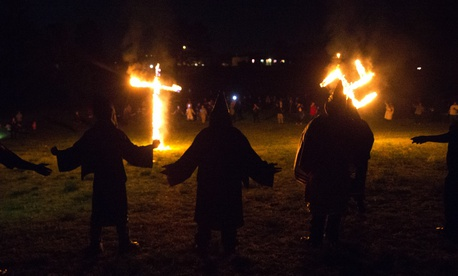 "In this Saturday, April 23, 2016 photo, members of the Ku Klux Klan participate in cross and swastika burnings after a ""white pride"" rally in rural Paulding County near Cedar Town, Ga."