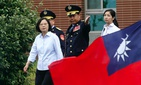 Taiwan's President Tsai Ing-wen, left, walks past a Taiwan national flag during an offshore anti-terrorism drill outside the Taipei harbor in New Taipei City, Taiwan, Saturday, May 4, 2019.