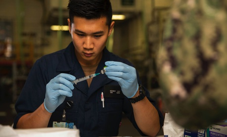 Navy Seaman Kenny Liu prepares a needle with a flu vaccination aboard the USS Gerald R. Ford in Newport News, Va., Oct. 22, 2019. The ship's crew received flu vaccines.