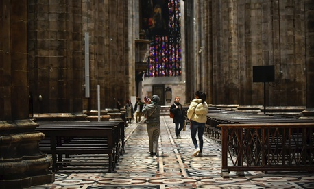 Tourists walk in the Duomo gothic cathedral after it was reopened following a closure due to the COVID-19 virus outbreak in northern Italy, in Milan, Monday, March 2, 2020.