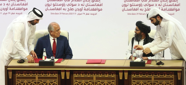 U.S. peace envoy Zalmay Khalilzad, left, and Mullah Abdul Ghani Baradar, the Taliban group's top political leader sign a peace agreement between Taliban and U.S. officials in Doha, Qatar, Saturday, Feb. 29, 2020.