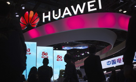 In this Oct. 31, 2019, file photo, attendees walk past a display for 5G services from Chinese technology firm Huawei at the PT Expo in Beijing.