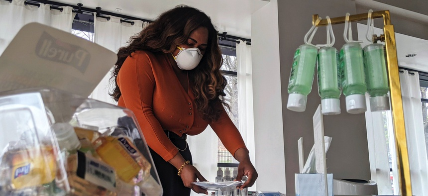 Adilisha Patrom, owner of a co-working and event space next to Gallaudet University, organizes face masks, hand sanitizer and other supplies inside her pop up shop on Thursday, March 5, 2020, in Washington, D.C.