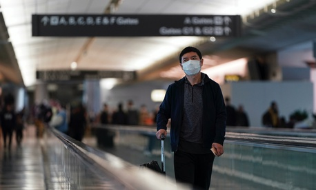 An airline passenger wearing a mask makes his way through the International Terminal at San Francisco International Airport Saturday, March 7, 2020, in San Francisco.