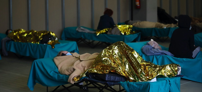 Patients lie on beds at one of the emergency structures that were set up to ease procedures at the Brescia hospital, northern Italy, Thursday, March 12, 2020.