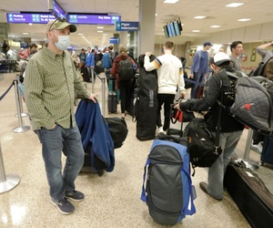 A masked traveler stands in line with his luggage before getting to the ticket counter at the Salt Lake City International Airport Sunday, March 15, 2020, in Salt Lake City.