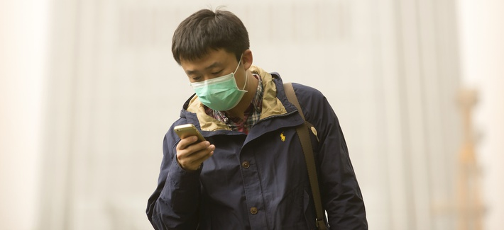 A man wears a face mask as he looks at his mobile phone during a dust and sand storm in Beijing, Thursday, May 4, 2017