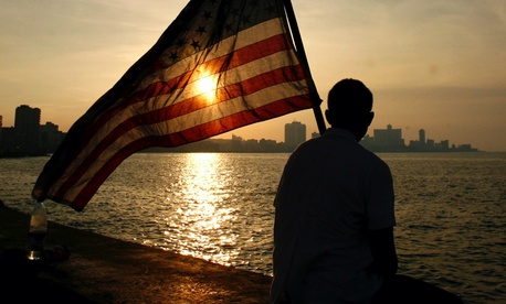 A Mexican-American, studying medical science in a Cuban university holds a U.S flag as he watches the sunset in Havana after a march to commemorate the 136th anniversary of the execution of eight students by the Spanish colonial government in 2007.