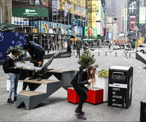A visitor ducks under a flock of flying pigeons in a sparsely populated Times Square, Friday, March 20, 2020, in New York. New York Gov. Andrew Cuomo is ordering all workers in non-essential businesses to stay home and banning gatherings statewide.