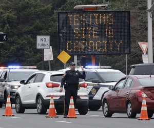 A police officer waves traffic past the entrance to a drive-through COVID-19 testing center after it reached capacity in Paramus, N.J., Friday, March 20, 2020.