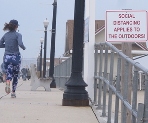 "This March 20, 2020 photo shows a jogger running past a sign on the Bradley beach, N.J. oceanfront urging people to use ""social distancing"" to maintain space between each other even in the outdoors during the coronavirus outbreak."