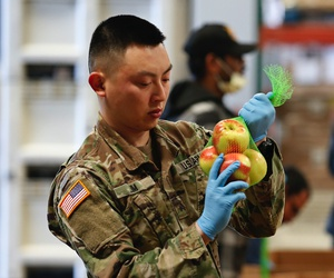 Sgt. Caleb Lim, of the California National Guard ties up a bag of apples at the Sacramento Food Bank and Family Services in Sacramento, Calif., Saturday, March 21, 2020.