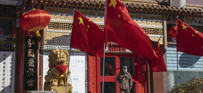 """In this photo taken Tuesday, March 3, 2020, a worker stands near Chinese national flag and propaganda which reads """"Go China"""" in Beijing."""