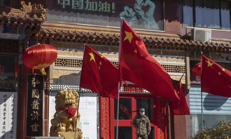 "In this photo taken Tuesday, March 3, 2020, a worker stands near Chinese national flag and propaganda which reads ""Go China"" in Beijing."