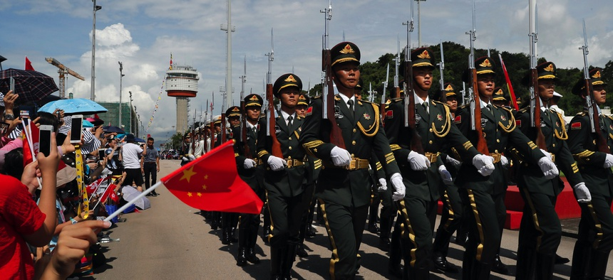 In this June 30, 2019, file photo, Chinese People's Liberation Army (PLA) soldiers take part in a flag raising ceremony during an open day of Stonecutter Island naval base, in Hong Kong, to mark the 22nd anniversary of Hong Kong handover to China.