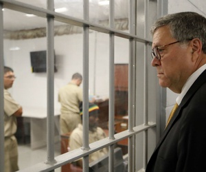 Attorney General William Barr watches as inmates work in a computer class during a tour of a federal prison in July 2019.