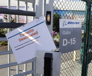 A sign warns of a deactivated employee turnstile at Boeing Co.'s manufacturing facility, Wednesday, March 25, 2020, in Renton, Wash., on the first day of a shutdown due to the spread of the new coronavirus.