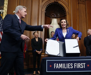 House Speaker Nancy Pelosi, accompanied by House Minority Leader Kevin McCarthy, and other legislators, participate in a bill enrollment ceremony for the CARES Act, after it passed in the House, on Capitol Hill, Friday, March 27, 2020 in Washington.