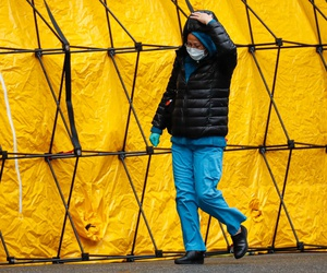 A medical worker walks past a COVID-19 testing tent tunnel set up outside the main entrance to the Department of Veterans Affairs Medical Center in New York.