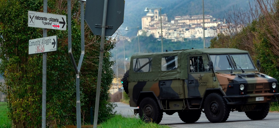An Italian Army vehicle blocks the road leading to the town of Contigliano, seen on the hilltop in the background, after it was declared a red zone due to its cases of Covid-19, the third red zone in the region of Lazio, Italy, Tuesday, March 31, 2020.