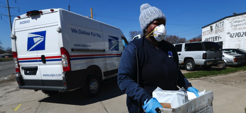 A United States Postal worker makes a delivery with gloves and a mask in Warren, Mich., Thursday, April 2, 2020.