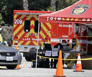 A coronavirus testing center for first responders operates in a parking lot for Dodger Stadium Monday, March 30, 2020, in Los Angeles.