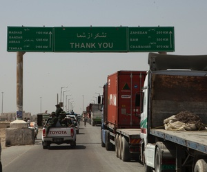 Trucks wait to cross the Afghanistan-Iran border in Zaranj, Afghanistan, May 10, 2011. The crossing is part of a busy trade route between Central Asia and the Middle East.