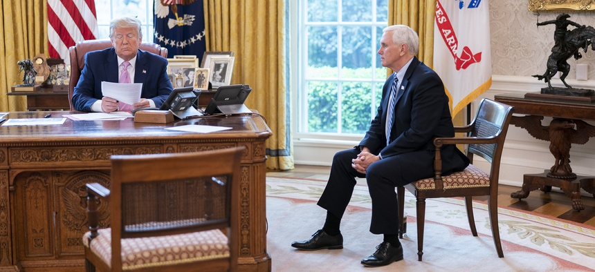 President Donald Trump and Vice President Mike Pence talk on the speaker phone with military family members about the military's coronavirus response, in the Oval Office, Wed., April 1, 2020.