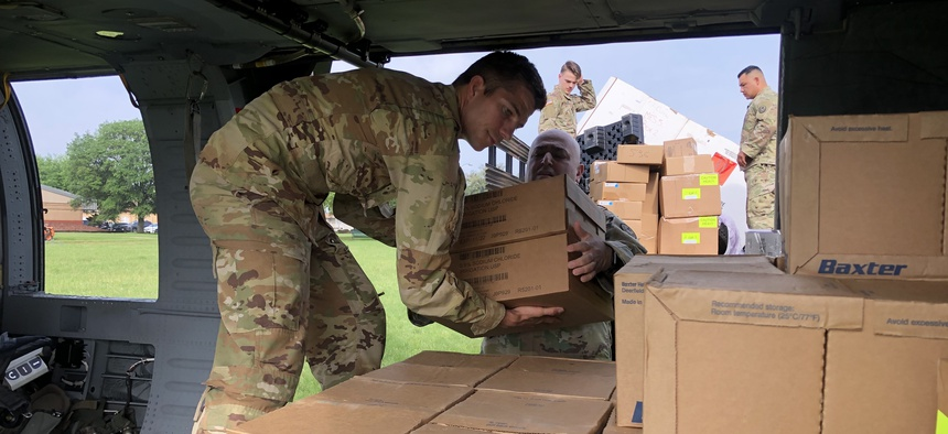 exas Army National Guard Soldiers load a UH-60 Black Hawk at Camp Mabry on April 8, 2020 with personal protective equipment for distribution in La Marque, Texas.