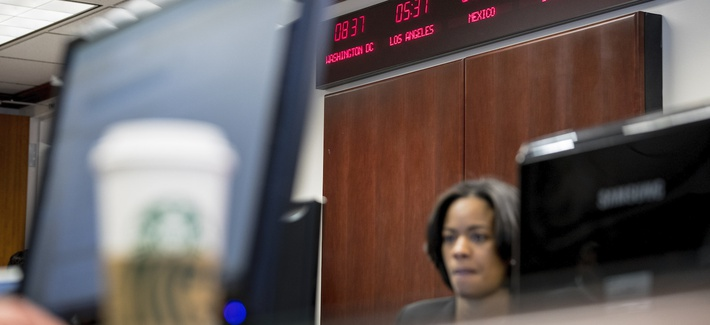 Digital clocks from different time zones around the world are displayed above Drug Enforcement Administration agents and intelligence analysts gathering information from field operations across the country at their command center. March 11, 2020