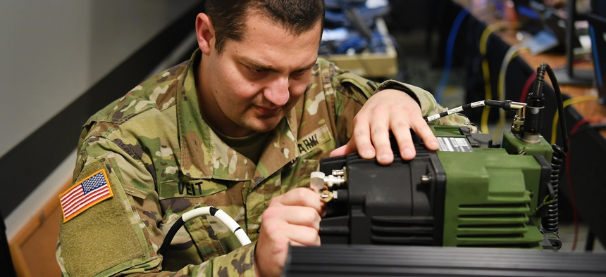 U.S. Army National Guard Pfc. John Veit, JTF 115th Regional Support Group information technology specialist, connects an amplifier for radio communication inside the Joint Operations Center (JOC) Apr. 09, 2020 at the Roseville Armory, Calif