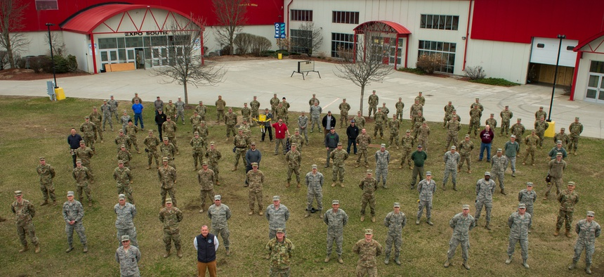 Airmen and soldiers of the Vermont National Guard, Vermont state employees, and contractors gather together for a group photo during the construction of a 400-bed alternate health facility in Essex Junction, Vt., April 5, 2020.