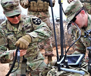 Staff Sgt. Christian Lehr and Staff Sgt. Trever Cooley, electronic warfare specialist with 2nd Brigade, 2nd Infantry Regiment, set up their portable packs which have capabilities of picking up and jamming enemy frequencies.