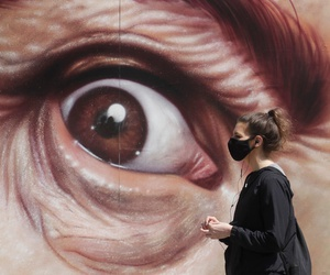 A woman wears a face mask while walking in front of a painting in San Francisco on Sunday.