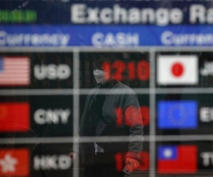 A man wearing a face mask is reflected on an electronic foreign currency exchange rates in downtown Seoul, South Korea, Tuesday, March 31, 2020.