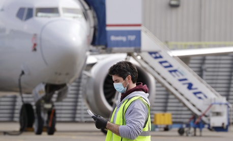 A worker walks past a Boeing 737 MAX jet at a Boeing airplane manufacturing plant Wednesday, April 29, 2020, in Renton, Wash.