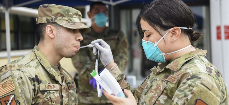 U.S. Air Force Staff Sgt. Melissa Lozada, 39th Medical Support Squadron resource management office non-commissioned officer in charge, right, checks a visitor's temperature, March 20, 2020, at Incirlik Air Base, Turkey.