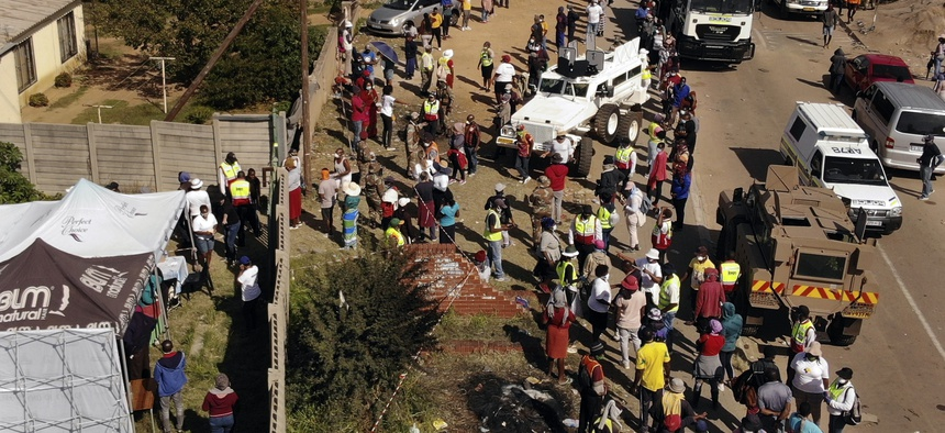 Thousands line up to receive food handouts in the Olievenhoutbos township of Midrand, South Africa, Saturday May 2, 2020. though South Africa begun a phased easing of its strict lockdown measures on May 1