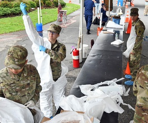Soldiers with the Louisiana Army National Guard's 256th Infantry Brigade Combat Team don protective suits as they prepare to administer nasal swabs to first responders and medical personnel at a mobile testing site in Westwego, Louisiana, March 21, 2020.