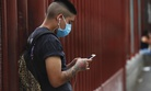 A man wearing a mask against the spread of the new coronavirus chats on his mobile phone outside a hospital in Iztapalapa in Mexico City, Thursday, April 30, 2020