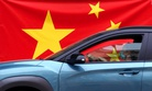 In this April 13, 2020, photo, a woman wearing a face mask drives her car by a Chinese flag placed on a street prior a curfew set up to help prevent the spread of the new coronavirus in Belgrade, Serbia.