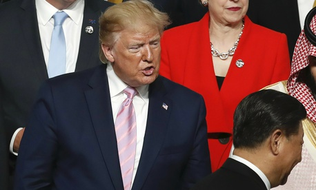 U.S. President Donald Trump, left, speaks to Chinese President Xi Jinping, bottom right, after they shook hands during family photo session at G-20 leaders summit in Osaka, Japan, Friday, June 28, 2019.