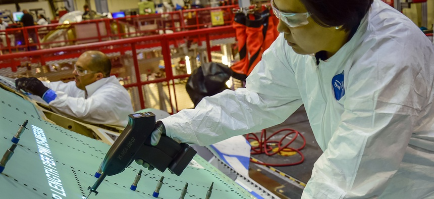 A Northrop Grumman technician assembles the fuselage of an F-35 Joint Strike Fighter.