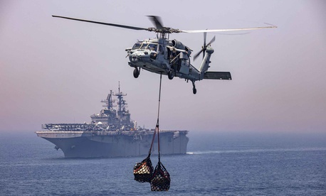 A Navy MH-60R Seahawk helicopter moves supplies near the USS Bataan during a replenishment in the Persian Gulf, April 25, 2020.